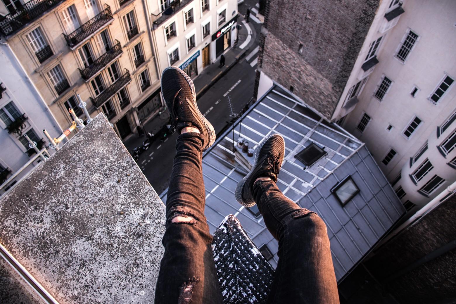personne assise sur le bord d'un toit d'un bâtiment