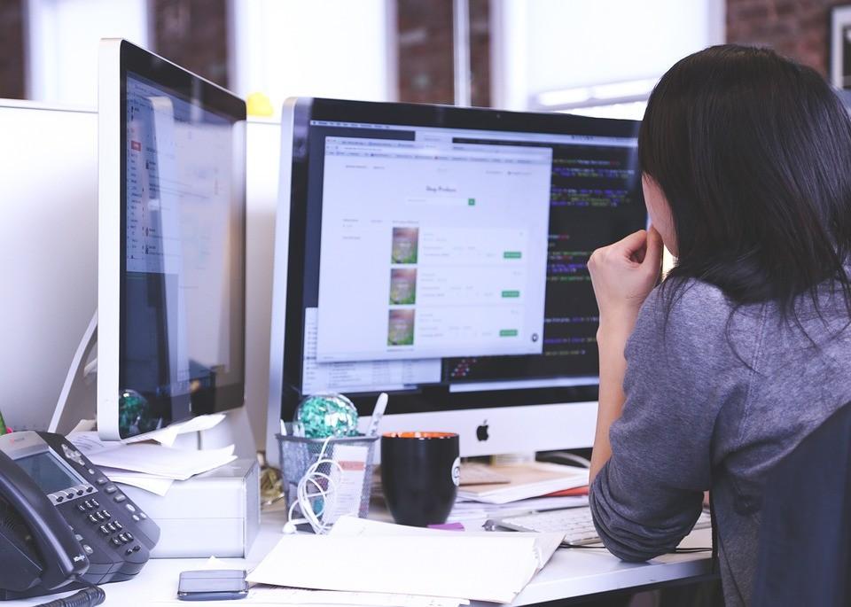 Femme de dos devant écran ordinateur