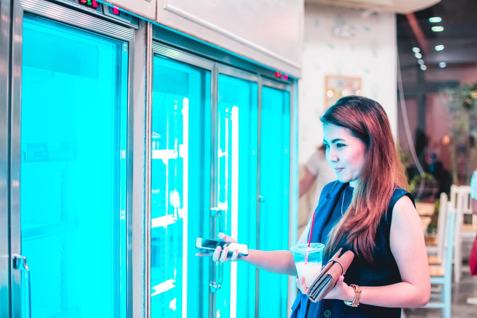 femme avec téléphone portable à la main au rayon surgelés magasin
