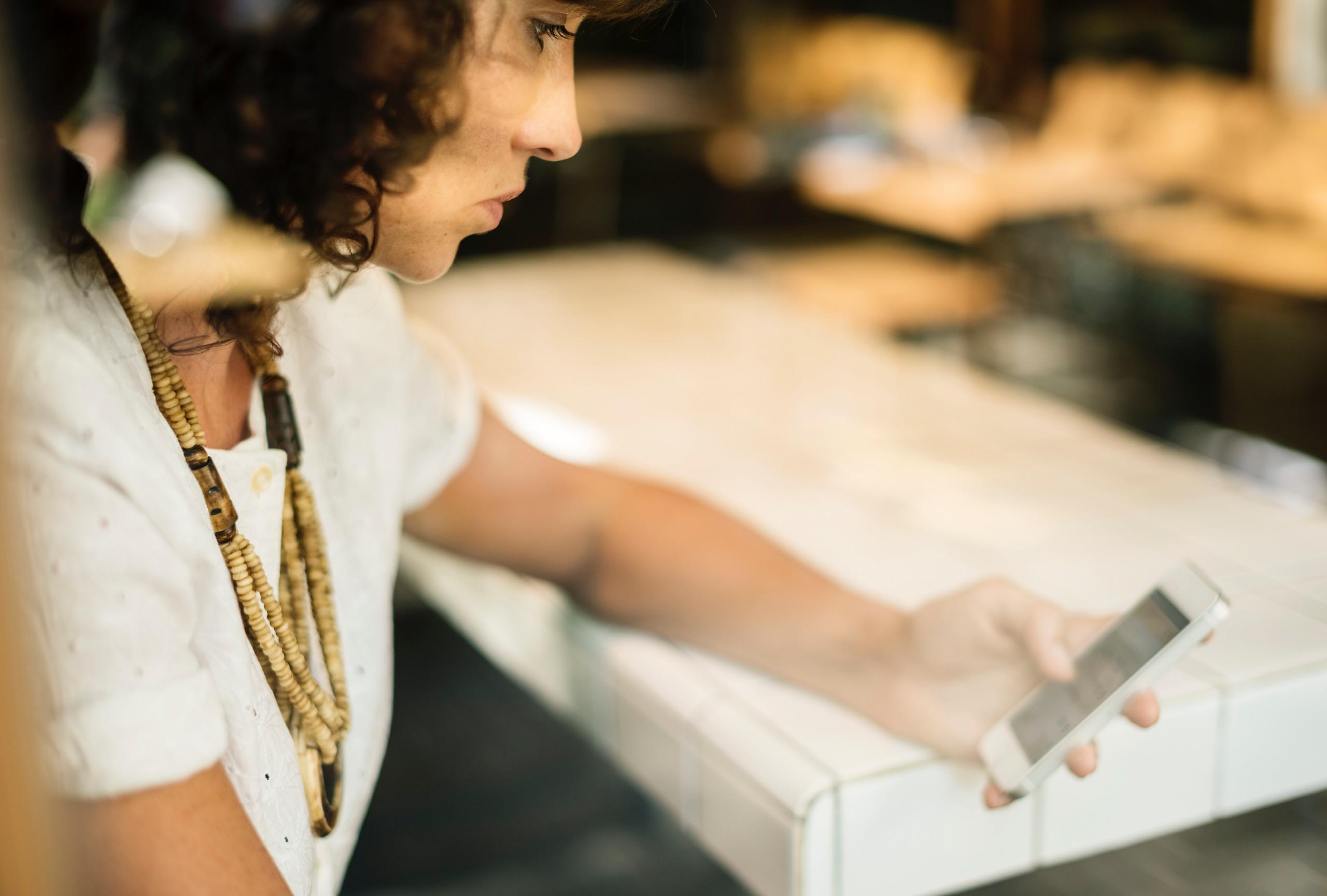 femme attablée regarde et tient téléphone main