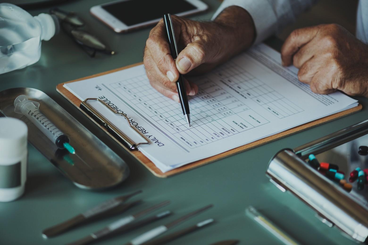 personne avec stylo dans la main remplit formulaire