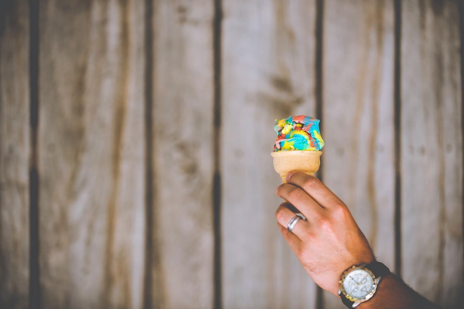 main tient cornet de glace multicolore