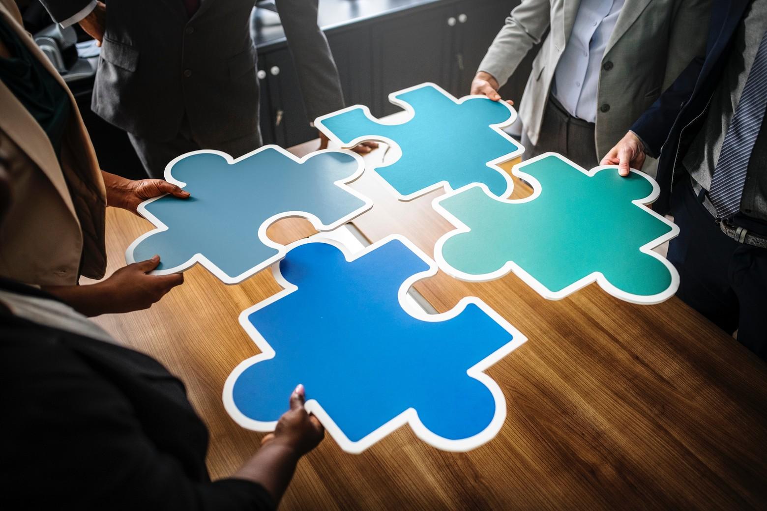 4 mains réunis au centre pièces puzzle