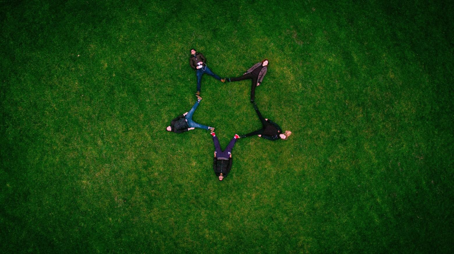 cinq personnes allongées sur l'herbe faisant signe étoiles