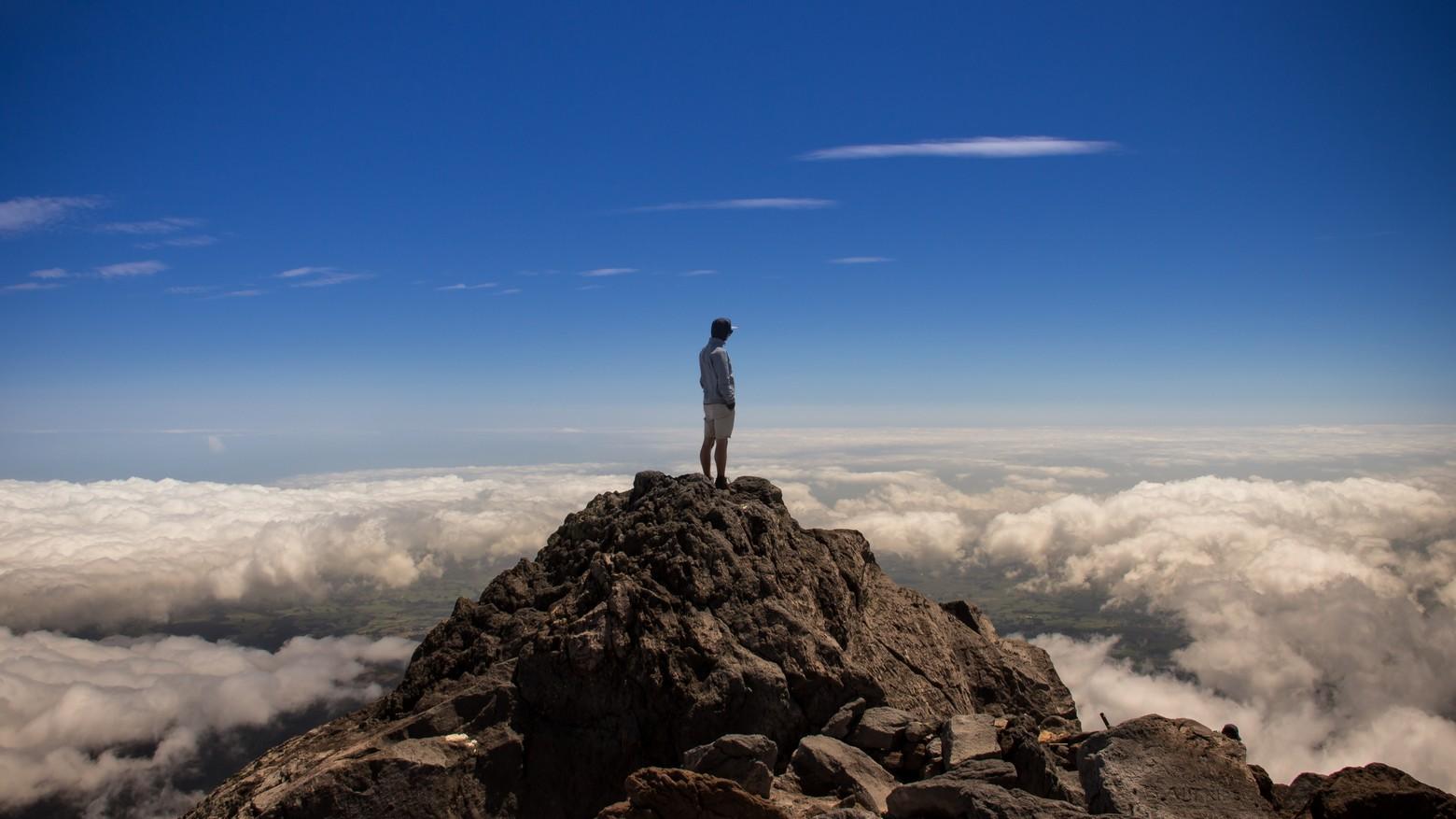 homme debout au sommet de la montagne