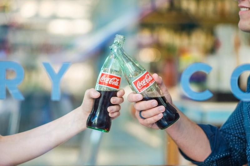 2 personne trinquent avec bouteille de Coca-Cola