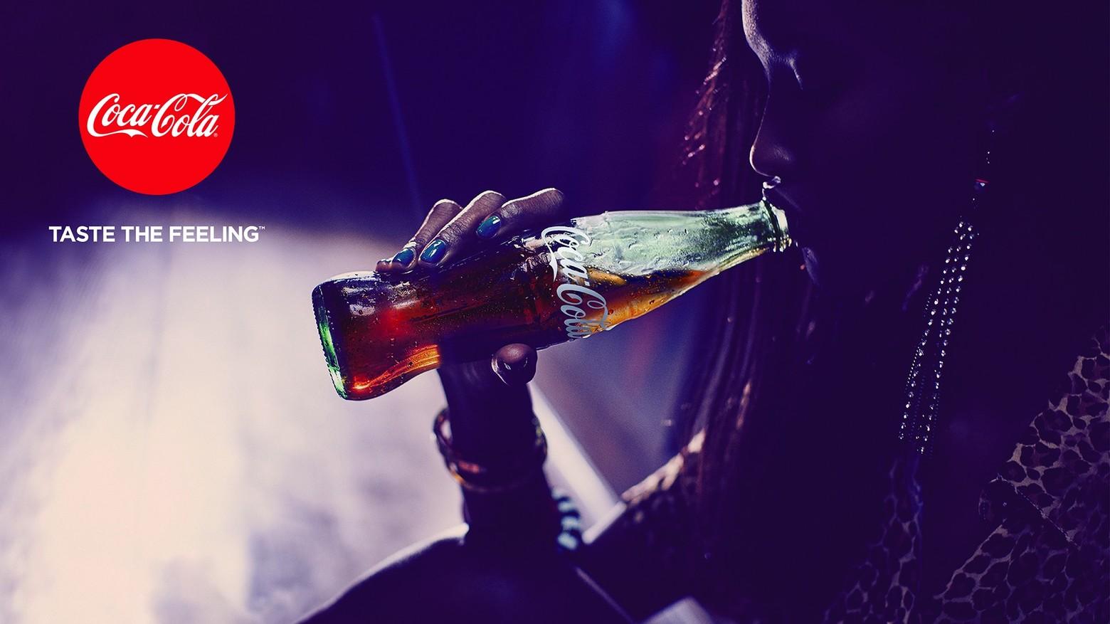 publicité personne tient Coca-Cola dans la main